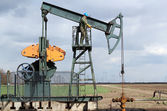 Oil and fuel industry oil worker standing on the pump jack — Stock Photo