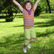 Happy little girl jumping in park — Stock Photo