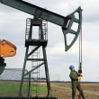 Oil worker check pumpjack - Stock Photo