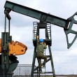 Stock Photo: Oil worker climbs to pumpjack