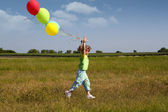 Little girl running with balloons — Stock Photo
