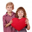 Little girl and boy posing with red heart — Stock Photo