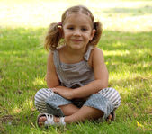 Little girl sitting on grass — Stok fotoğraf