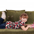 Stock Photo: Little girl lying on bed with laptop