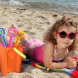 Little girl with sunglasses on the beach - Stock Photo
