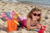 ビーチでサングラスを持つ少女 — ストック写真