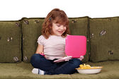 Little girl sitting on bed with laptop — Stock Photo