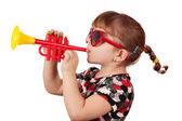 Malá holčička se slunečními brýlemi hrát trubku — Stock fotografie