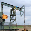 Stock Photo: Oil worker standing at pump jack