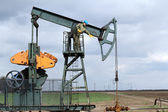 Oil worker standing at pump jack — Stock Photo