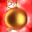 Christmas ball and serpentine on red background — Stock Photo