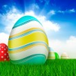 Easter eggs on grass and blue sky background — Stock Photo