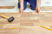Installing wooden laminate flooring — Stock Photo