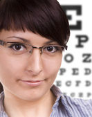 Woman with glasses, eye chart in background. At the Optician — Stock Photo