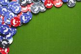 Gambling chips on green felt — Stock Photo