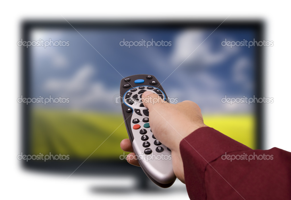 Hand holding TV remote control with a television in the background. Close up. — Stock Photo #9797815