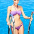 Cute woman standing on pool ladder — Stock Photo #10007917