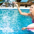 Happy woman splashing water in pool — Stock Photo