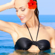 Woman with red flower in swimming pool - Stock Photo