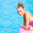 Stock Photo: Young woman in swimsuit lying close to pool