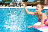 Gelukkige vrouw spatten in zwembad — Stockfoto