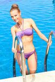 Mulher sexy em pé na escada da piscina — Fotografia Stock