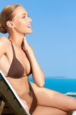 Cute woman sitting on sunbed and smiling — Stock Photo