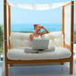 Woman with laptop on canopied seat — Stock Photo #10066987