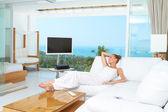 Woman relaxing in spacious bright living-room — Stock Photo