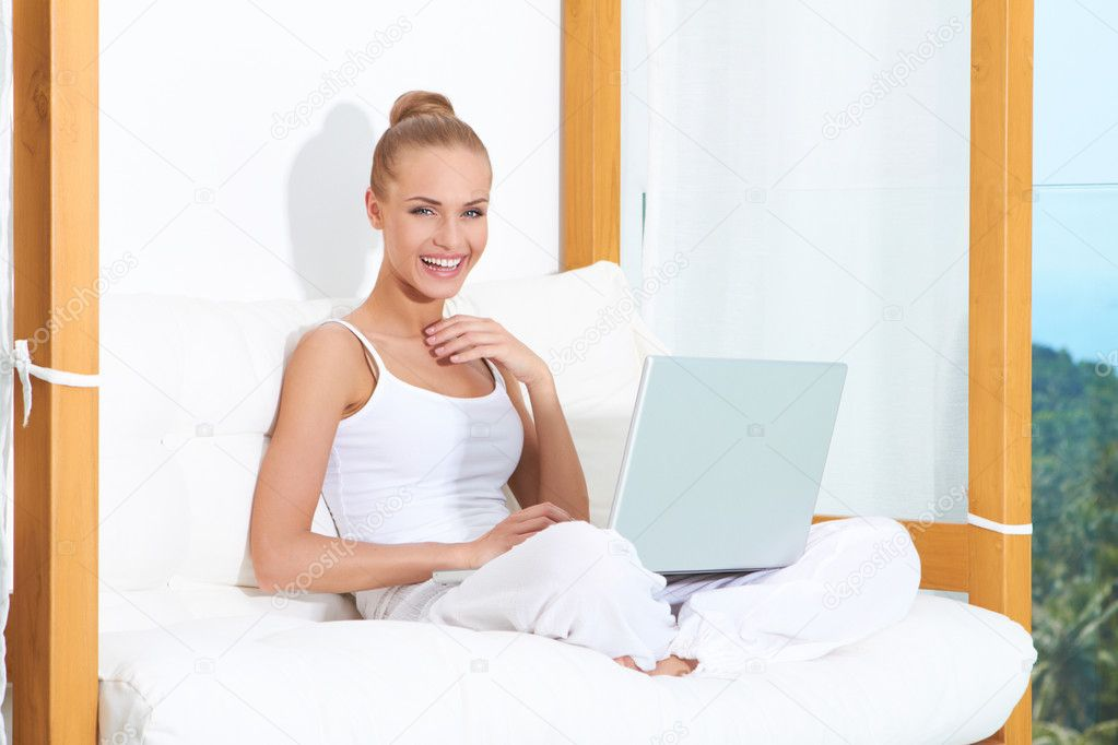 Joyful woman seated on white cushions laughing with with her laptop balanced on her crossed legs  Stock Photo #10066926