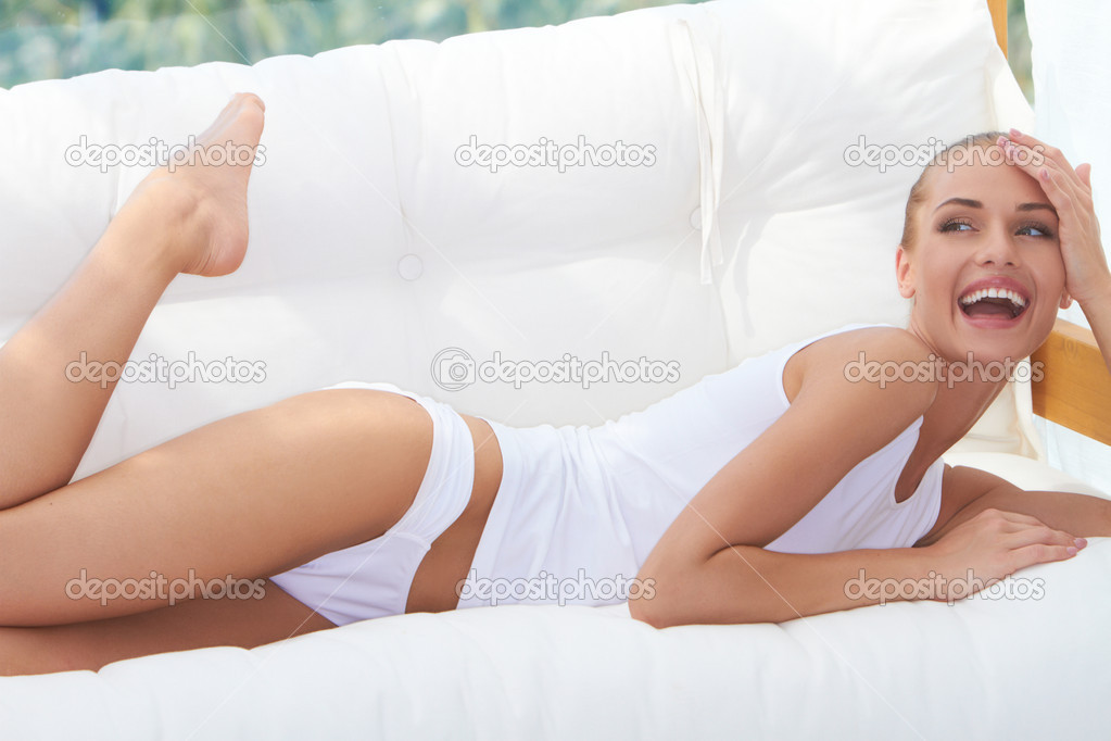 Laughing woman in panties and a tight fitting white shirt lying on her stomach on a bench with cushions looking back over her shoulder — Stockfoto #10066983