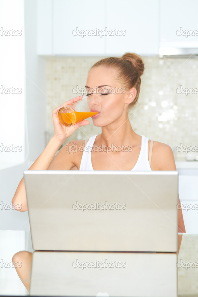Healthy happy woman drinking from glass of fresh orange juice seated at a table using her laptop — Stock Photo #10066992
