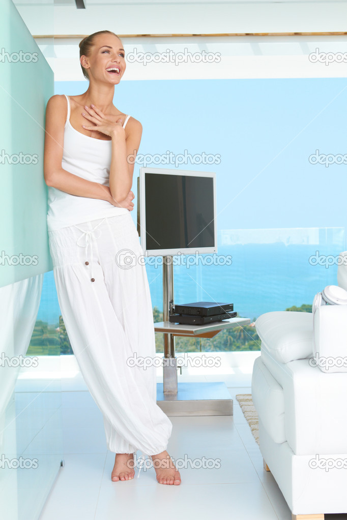 Woman standing laughing in casual white outfit in a modern glass fronted living room with a view of the ocean — Stock Photo #10067028