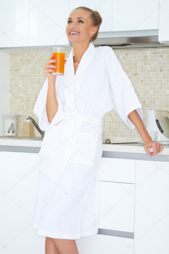Glamorous woman in a white bath robe enjoying a large glass of fresh orange juice for breakfast — Stock Photo #10067069