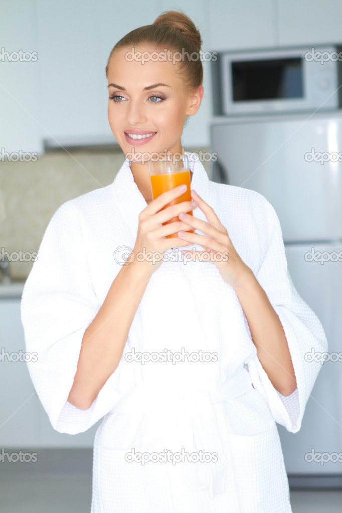 Stylish woman in a thick white towelling gown drinking a large glass of healthy orange juice — Stock Photo #10067080