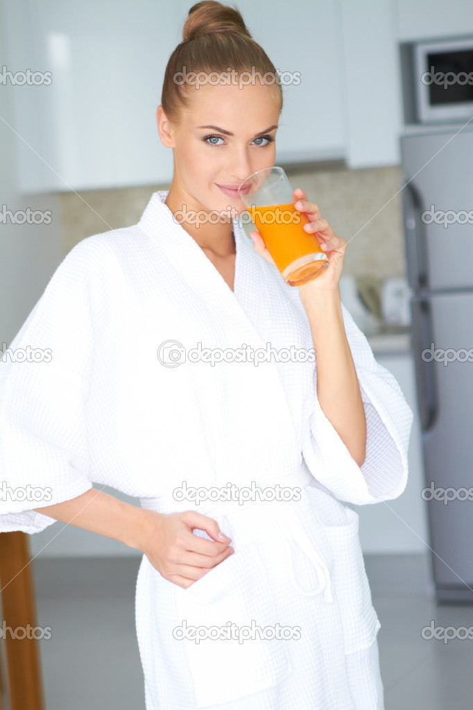 Beautiful elegant woman in a white bath robe drinking a large glass of fresh orange juice  Stock Photo #10067090