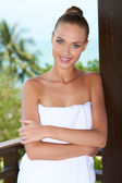 Beautiful woman wrapped in white towel — Stock Photo