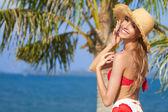 Joyful girl in red bikini posing at the beach — Stock Photo