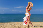 Smiling woman in straw hat on sandy beach — Stock Photo