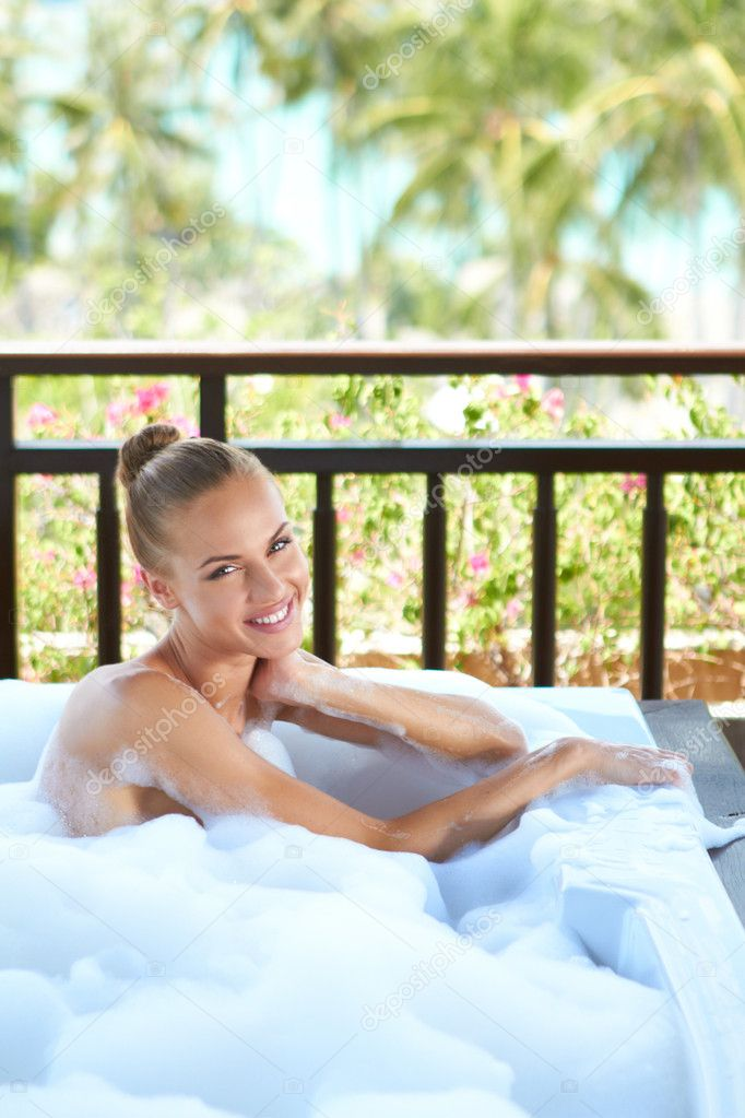 Beautiful elegant blonde woman sitting relaxing in an open-air tropical bubble bath — Stock Photo #10244852