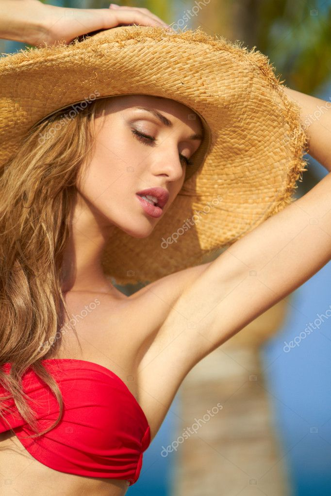 Sexy woman with arms raised wearing hat and red bikini — Stok fotoğraf #10245114