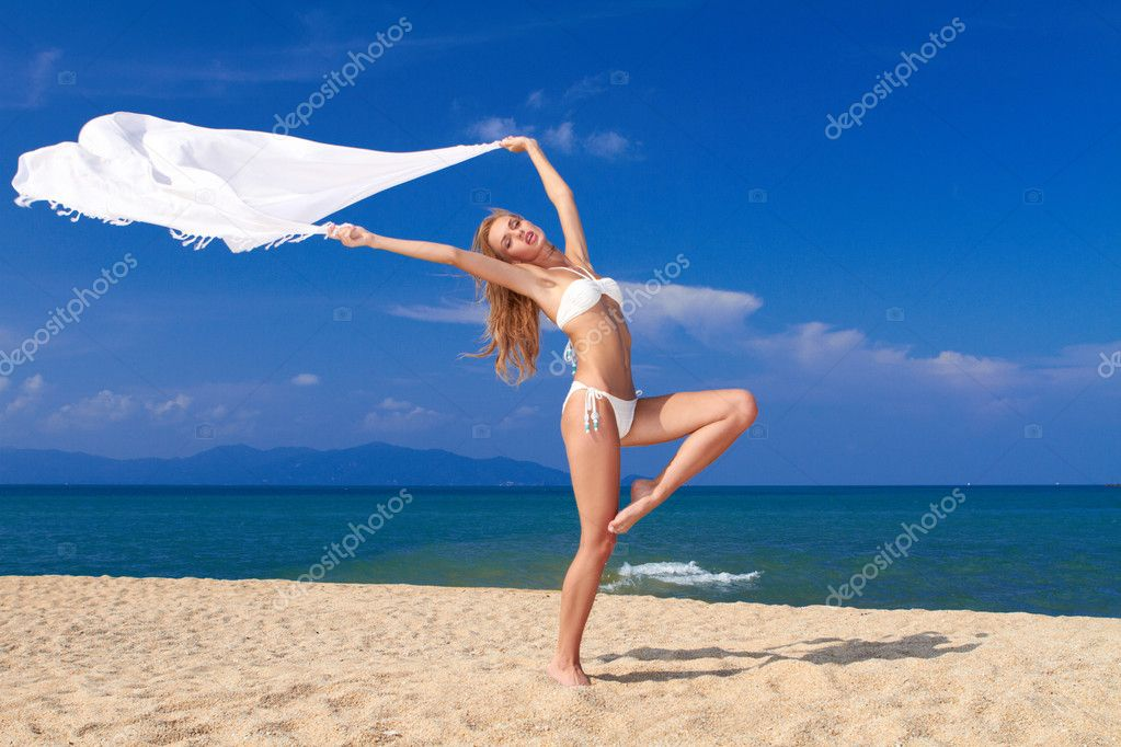 Bikini clad blonde beauty in a dancers pose on soft white sand with the ocean in the background  Stock Photo #10245375