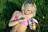 Beautiful blond woman outdoorlying on grass — Stock Photo