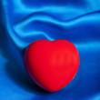 Red heart lying on blue silk textile with copy space — Stock Photo