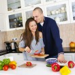 Portrait of a smiling couple preparing food together at home — Stock Photo