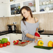 Portrait of a young woman doing a salad in her kitchen, while co — Stock Photo