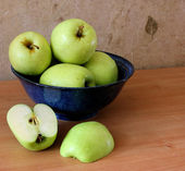 Apples in a blue bowl with a sliced apple — Stock Photo