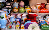 Colourful ceramic tableware in a market stall — Stock Photo