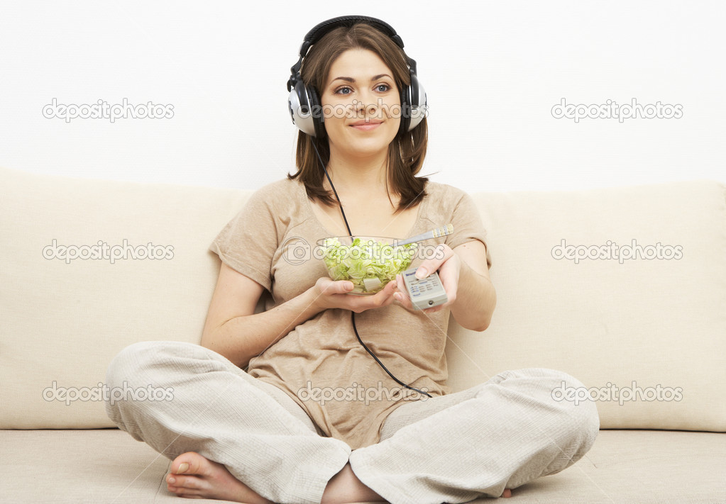 Girl watches TV and eats salad. sitting on sofa. headphones on head — Stock Photo #8737048