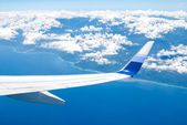 Airplane fly over land and ocean — Stock Photo